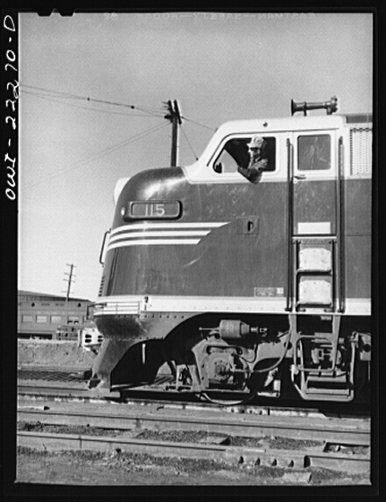 Winslow, Arizona. Fireman in the cab of a Atchison, Topeka, and Santa Fe Railroad diesel freight locomotive which has just come out of the roundhouse