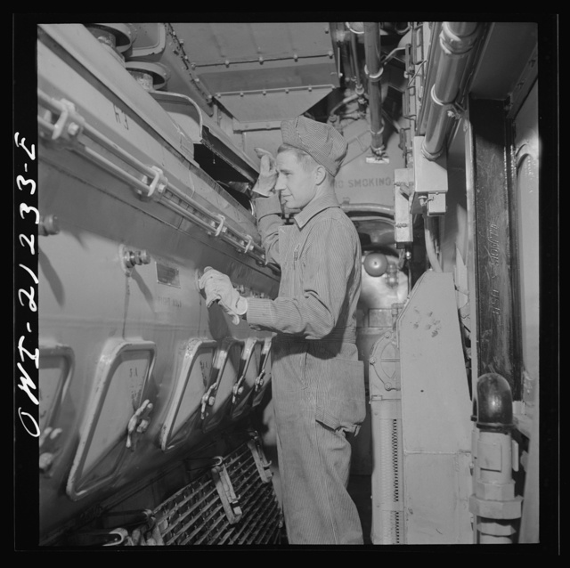 Winslow, Arizona. W.F. Leverenz, maintainer, at work on one of the units of the diesel freight locomotive in the Atchison, Topeka and Santa Fe Railroad yard