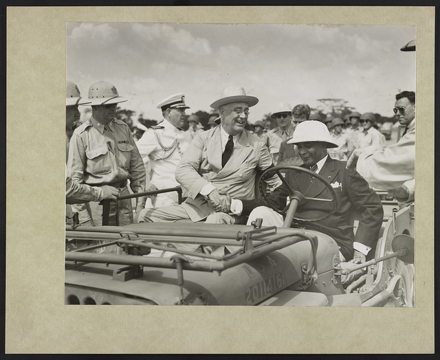 With a warm handclasp, President Roosevelt welcomes President Edwin Barclay of Liberia to an American jeep as they begin a review of American Negro troops stationed in the strategic African Republic