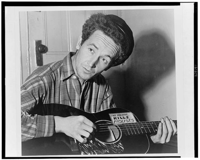 [Woody Guthrie, half-length portrait, seated, facing front, playing a guitar that has a sticker attached reading: This Machine Kills Fascists] / World Telegram photo by Al Aumuller.