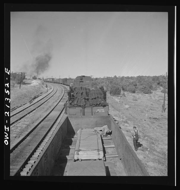 Yampai, Arizona. Brakeman and the conductor inspecting the train during a stop on the Atchison, Topeka, and Santa Fe Railroad between Seligman, Arizona and Needles, California