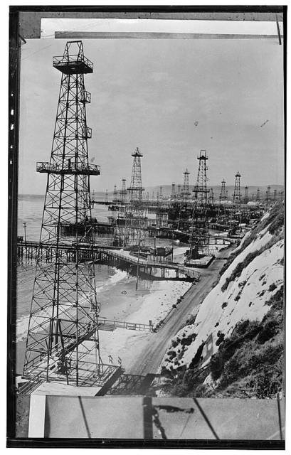 America's petroleum industries pour out fuel and lubricants for the United Nations. Oil well derricks on the beach along the coast of the U.S. Pacific coast state of California indicate how thorough is the seach for oil which has been going on in America for more than eighty years. Some beach wells are drilled straight down to reach oil deposits, but others are drilled at an angle so that oil is being pumped from locations far under the sea. Sometimes the bottom of the well is a quarter mile or half mile from the shore, while surf washes the foundations of the steel tower on which the drilling or pumping machinery is placed. The thoroughness and efficiency of the U.S. oil industry in finding new oil deposits accounts for the enormous supplies produced in America for the modern machines of war. In 1944 according to a U.S. oil company official, the predictable U.S. crude oil total will reach 1,601,250,000 barrels