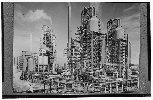 "America's petroleum industries pour out fuel and lubricants for the United Nations. These three new catalytic oil ""cracking"" units are turning out gasoline for the new machines of war at the plant of a large U.S. refining company in the southern U.S. state of Louisiana. In the eight years of the development of the ""cracking"" process in producing gasoline, it is estimated that 1,000,000,000 barrels of crude oil have been saved by the oil industry. The ""cracking"" process subjects crude oil to heat and pressure by which the oil molecules are broken down and made to release more of their derivable elements. The drain of war on such gasoline producing units as these is shown by the fact that the U.S. has manufactured 180,000 planes since December 7, 1941, propelled by gasoline motors. For example, one U.S. Liberator four-motored bomber in a six-hour bombing run consumes 1,800 gallons of gasoline, enough to last the average U.S. civilian motorist from three to five years"