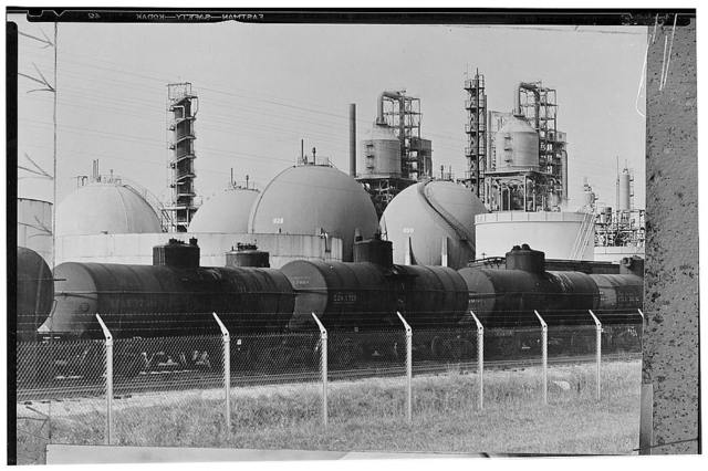 America's petroleum industries pour out fuel and lubricants for the United Nations. Railroad cars stand on a side track ready to receive cargoes of gasoline stored in large spherical tanks at the refinery of one of the principal U.S. oil companies. The cars will speed the gasoline across the American continent to seaports where it will be loaded onto tanker ships for conveyance overseas to the armed forces of the United Nations. Gasoline totals have reached new records since the U.S. entered the war. Besides the enormous amounts required to fuel the 180,000 planes American factories have turned out since December 7, 1941, large supplies of fuel are needed for naval vessels, merchant ships, tanks and mechanized units in the field. It takes 25,000 gallons of gasoline to move a single U.S. Army tank division 100 miles (160 kilometers)