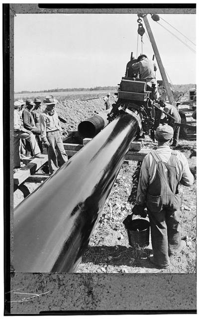 America's petroleum industries pour out fuel and lubricants for the United Nations. The largest oil pipeline ever laid runs from the U.S. southwest state of Texas eastward to the Atlantic coast, a distance of almost 1,400 (2240 kilometers) miles, over which 300,000 barrels of oil every day is being pumped to help supply the enormous war demands of the armed forces of the U.S. and the United Nations. The pipeline is 24 inches in diameter and cost $95,000,000 to complete. The section being laid in the ground has been given a coat of hot asphalt paint. The building of the pipeline insured a steady flow of fuel oil from the oil fields to Atlantic coast ports