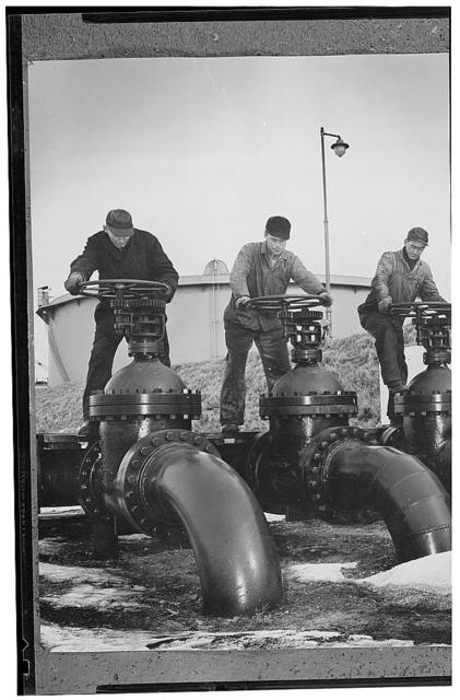 America's petroleum industries pour out fuel and lubricants for the United Nations. Men at the wheels of large valves regulate the flow of oil into oil tankers at a U.S. Atlantic coast seaport. The oil, flowing from large storage tanks on the dock, is being transhipped to the armed forces of the U.S. and other of the United Nation. Through valves like these pour the derivative products of some of the 1,601,250,000 barrels of oil which the U.S. oil industry will produce this year. The fact that a U.S. Liberator four-motored bomber consumes 1,800 gallons of gasoline in one six-hour bombing run, enough to supply the average citizen motorist with fuel for four or five years of motoring, indicates the heavy volume of oil supplies required in the modern war