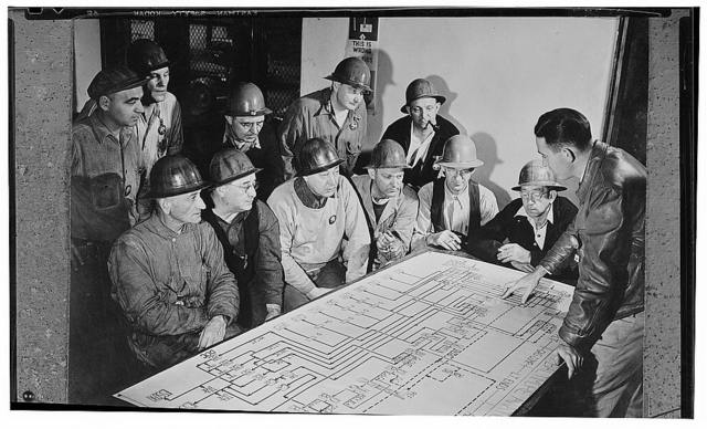 """America's petroleum industries pour out fuel and lubricants for the United Nations. An """"oil flow chart,"""" showing the course of oil through a modern plant, is being studied by men of an oil """"cracking"""" unit in the U.S., while an expert explains to them the intracacies of the chart. Large oil """"cracking"""" plants, for the rapid production of aviation gasoline and other products, are one of the most recent developments in the refining phase of the oil industry in the United States. Crude oil in these units, when subjected to great heat and pressure, is forced to give up more of its derivable elements than by former methods of refining. The process """"cracks"""" or breaks down the crude oil molecules. In the last eight years since the process was put into operation more than 1,000,000,000 barrels of crude oil, it is estimated, have been saved by the large quantities of crude oil products now being made available to the combat units of the U.S. and her allies"""