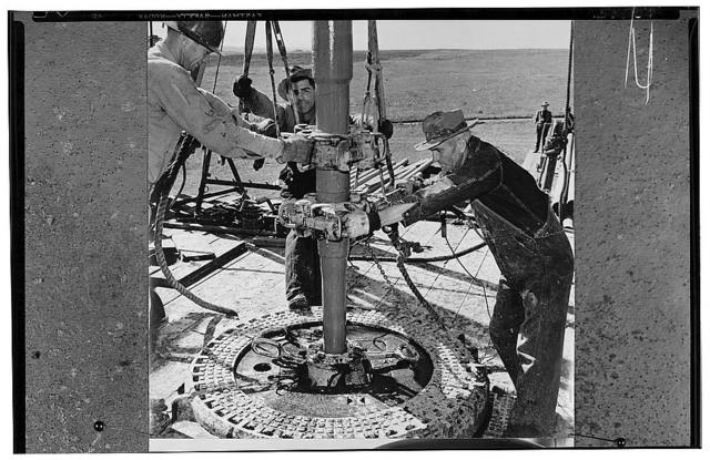 "America's petroleum industries pour out fuel and lubricants for the United Nations. At an oil well in the U.S. Southwest state of Oklahoma, oil drillers are using tools called ""tongs"" which are clamped on the drill stem to screw on a new section of stem or to unscrew the stem, section by section, after the drilling far below the earth's surface is finished. This procedure is common in modern rotary drilling for oil . The well pictured here is being drilled by a ""wildcat"" organization of drillers, which means they are formed in a group independent of any of the great oil companies. The well, if successful, will contribute to the vast quantity of oil being poured overseas to the U.S. armed forces and the United Nations for the successful waging of the war. The predictable total of U.S. oil production in 1944, according to a U.S. oil company official, is 1,601,2500,000 barrels produced by thousands of wells such as this one. Some U.S. oilwells today are drilled to a depth of three miles (4.8 kilometers) underground"