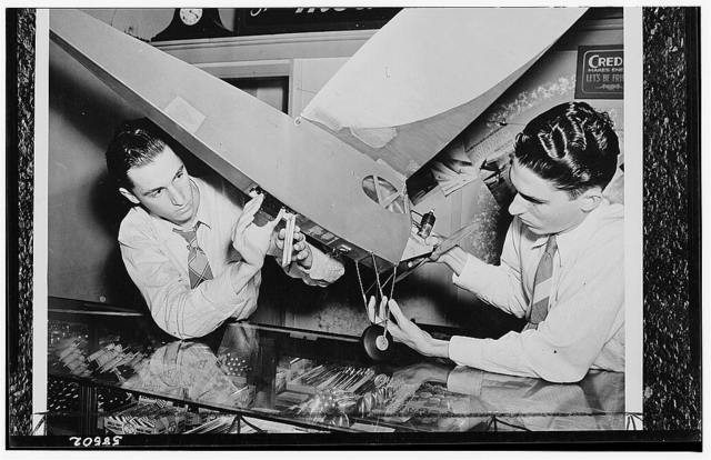 America's youth builds and flies model planes on miniature flying fields. Two American brothers proudly display their model of a photographic reconnaissance plane. They designed and constructed this small plane which takes photographs through a trap-door installed in the fuselage. Controlled by a time release, the trap door opens in mid-air and operates the shutter of a camera mounted in the plane. Model building has long been a popular hobby of American youth. In 1941 it was estimated that nearly three million boys were actively interested in model building. The National Aeronautics Association through its model divisions, the Academy of Model Aeronautics, has formed an Air Youth Division to bring a coordinated activity in aviation to American youngsters. Post war plans include an Inter-American Model contest to bring the young model builders of South American countries, the U.S. and Canada into friendly competition