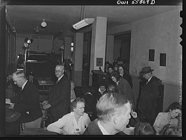 Arlington, Virginia. Citizens being checked to verify payment of poll tax and proper registration before receiving ballots for the national presidental election. A fire hose wagon is in the background of the firehouse where the voting is taking place