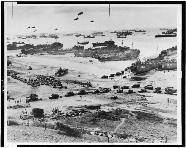 [Bird's-eye view of landing craft, barrage balloons, and allied troops landing in Normandy, France on D-Day] / U.S. Maritime Commission photo.