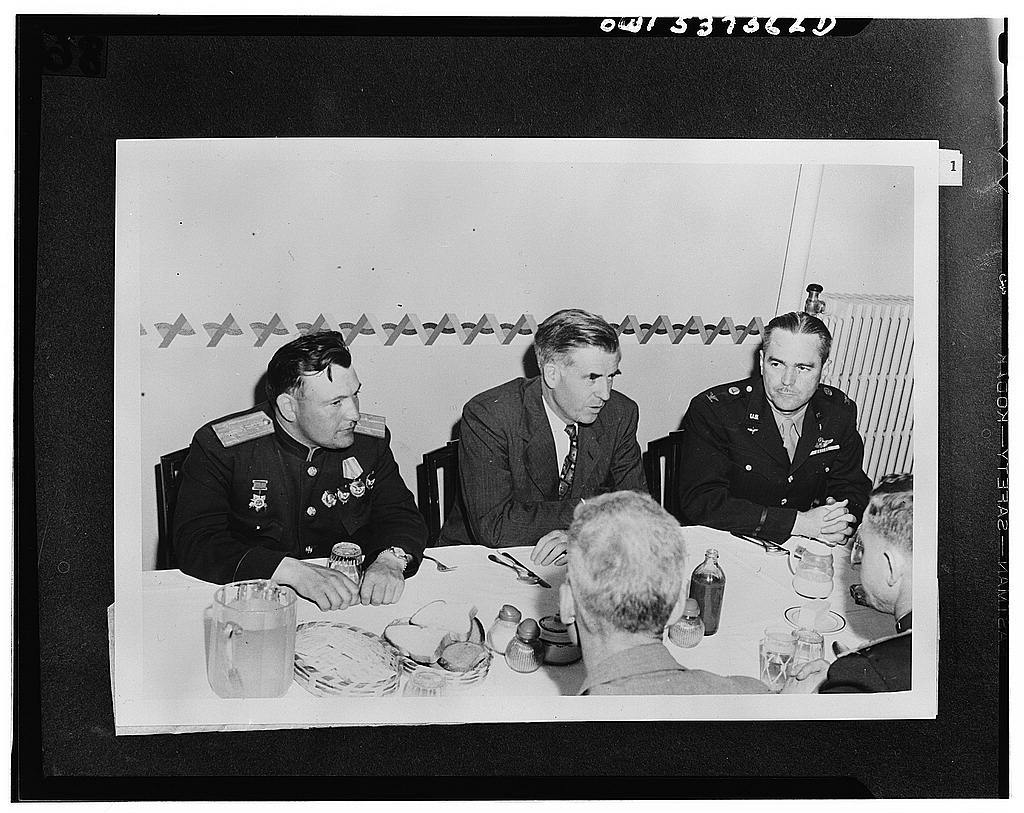 Fairbanks, Alaska. Vice President Henry A. Wallace, returning from China and Siberia, dining at Ladd Field with Russia and and American airmen who fly lend-lease planes to Russia through the Alaskan wing of the Air Transport Command. Left to right: Colonel N.S. Vasin, commanding officer of the Russian Air Force's first aviation ferrying regiment, who is stationed at Nome, Alaska; Mr. Wallace; Colonel Russell Keiller, commanding officer of Ladd Field