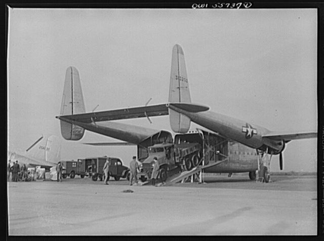 Large truck being driven off the Army Air Forces' new C-82 which was shown for first time at demonstration of equipment held by United States Army Air Forces. The special function of this plane is to land heavy military loads safely on rough fields near battle points. Its range exceeds 3,500 miles