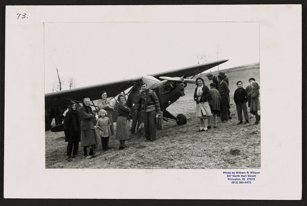 [Lieutenant Bill Wilson (center, holding a Jerrican) posed by an airplane with a group of local people, Dijon, France]