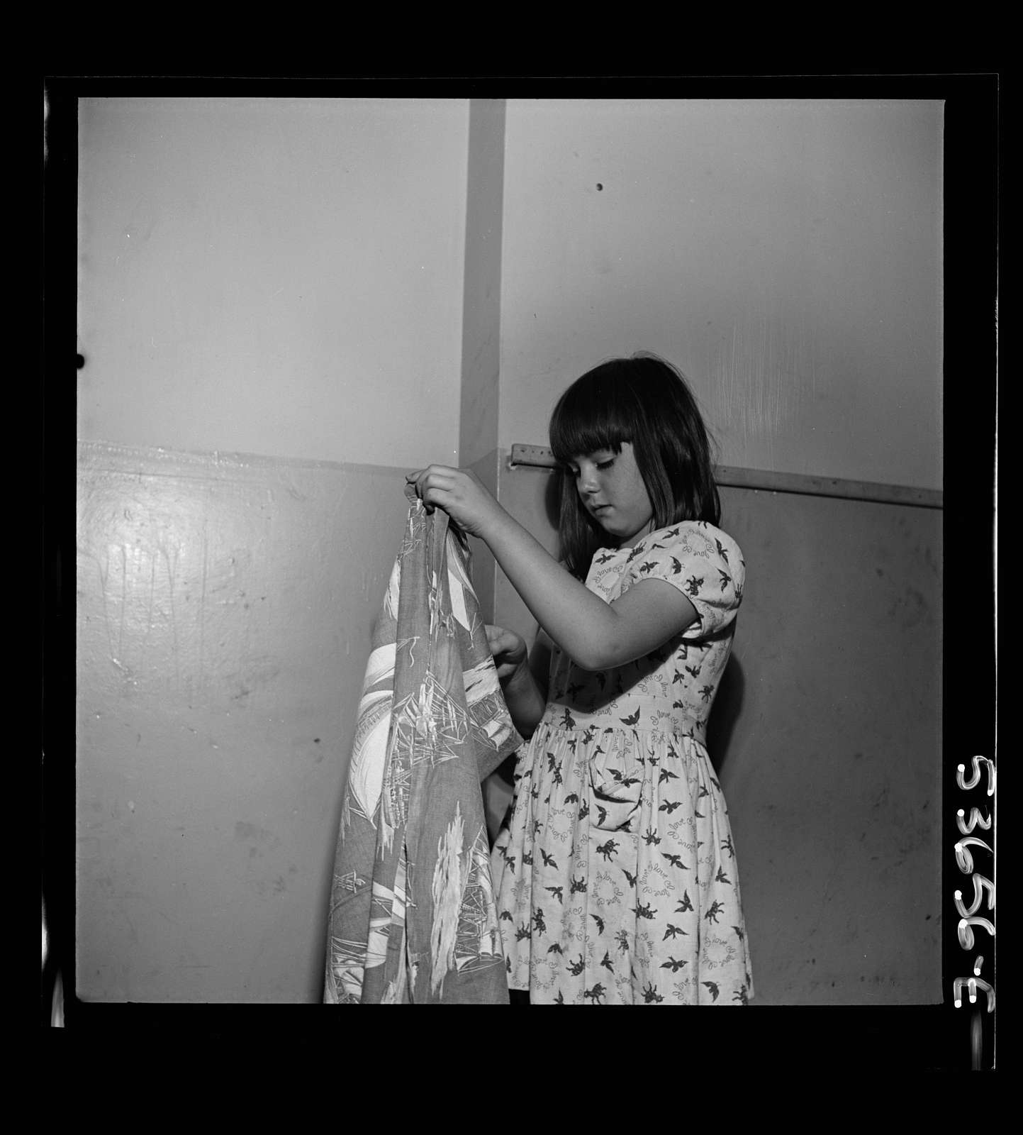 New York, New York. A little girl folding a blanket after a rest period at Greenwich House where she and many children receive day care while their mothers work. They enjoy work in clay, games, etc. as well as rest in this neighborhood center