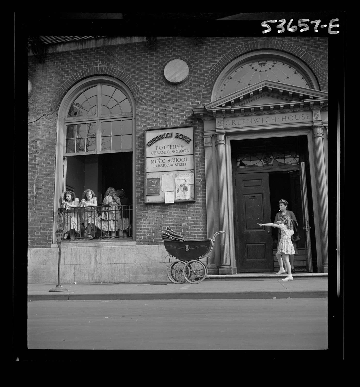 New York, New York. A mother and child at the Greenwich House entrance where the little girl receives day care while her mother works