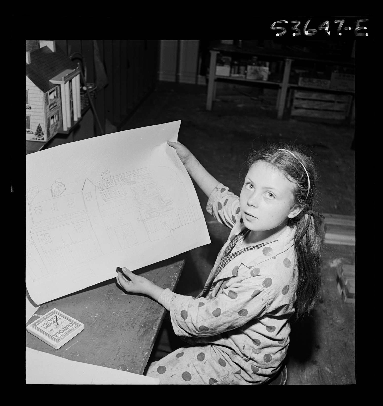 New York, New York. A working mother's child who receives day care after school and on Saturdays at Greenwich House, proudly displaying her version of the ideal home, complete with a garage, victory garden and tree-shaded lawn