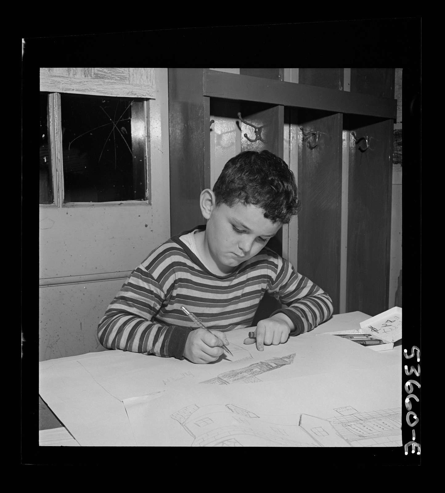 New York, New York. A young draftsman drawing plans for a house and developing his favorite hobby at Greenwich house where he received day care while his mother works