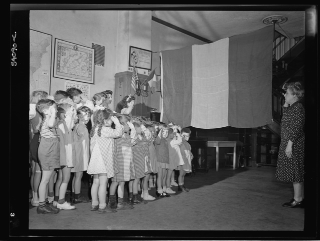 New York, New York. June 6, 1944. Preschool age children at L'Ecole maternelle francaise on D-day saluting the French flag
