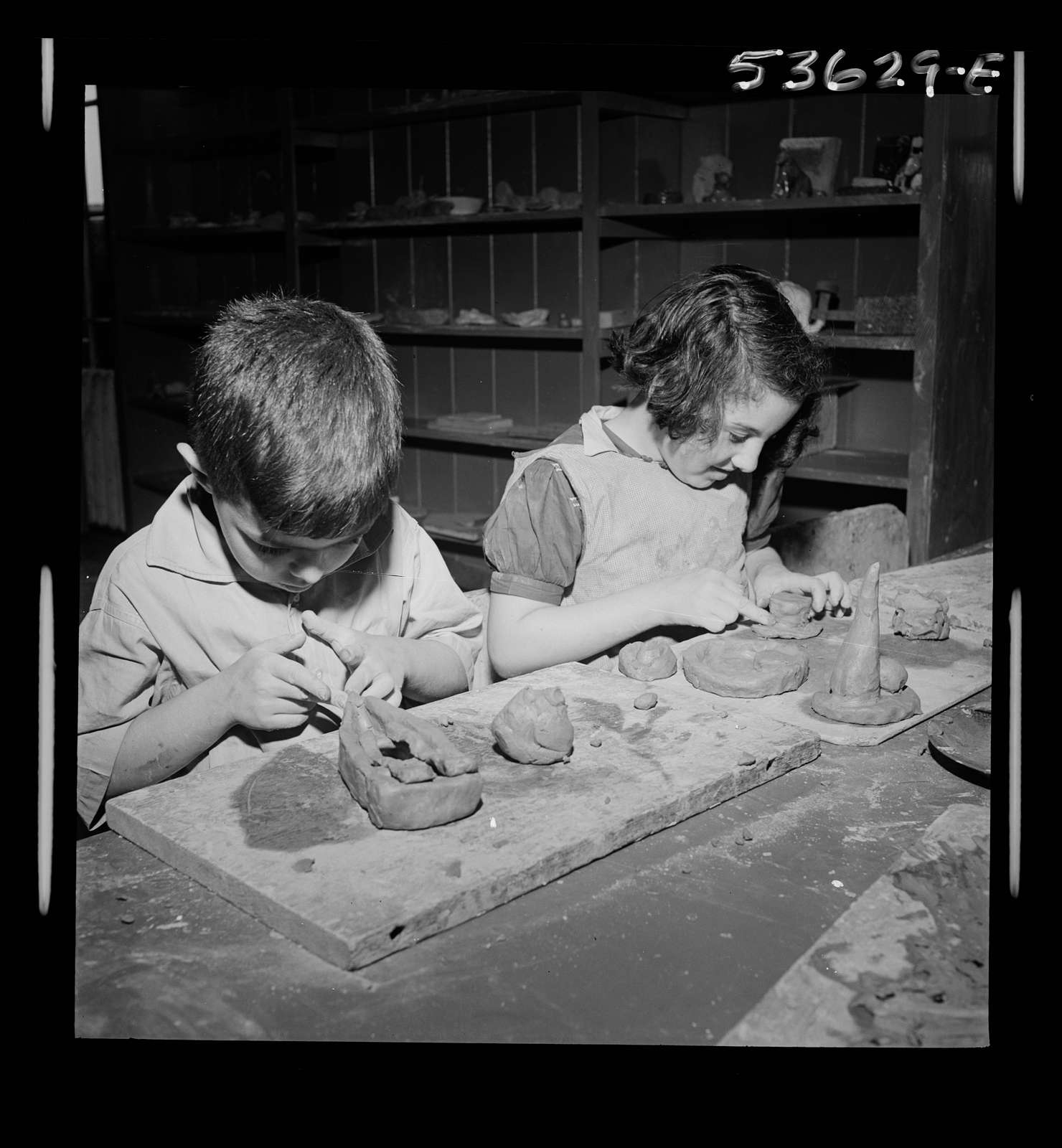 New York, New York. Two children of working mothers, developing their favorite hobbies during after school hours at Greenwich houses where they receive day care until the mothers call for them