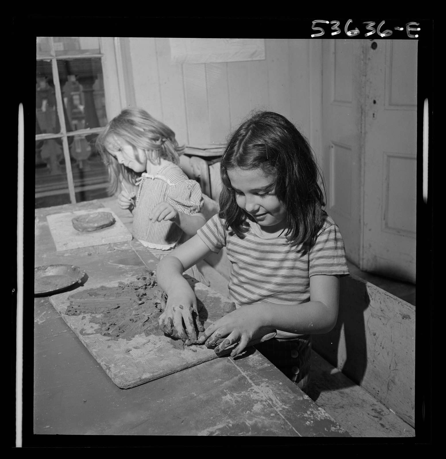 New York, New York. Two children of working mothers who receive day care at Greenwich House enjoying their work in clay. They also enjoy singing and dancing and rest in after school hours at this neighborhood center