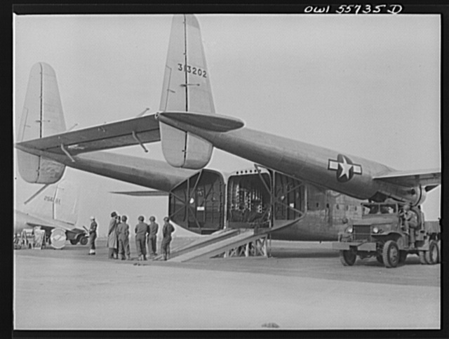 Rear view of new C-82 showing twin boom tail and square interior. This is the first war plane designed solely for hauling military cargo. It is in the 50,000 pound class and in its weight and bulk carrying capacity, will enable the air transport of ninety percent of the heavy equipment of a standard triangular Infantry Division. It may be used to carry troops, paratroops, and equipment up to the size of tanks