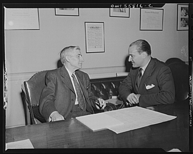 Washington, D.C. Mario Verdi (left), OWI (Office of War Information) radio commentator for Italy, visiting Assistant Postmaster General Perdum
