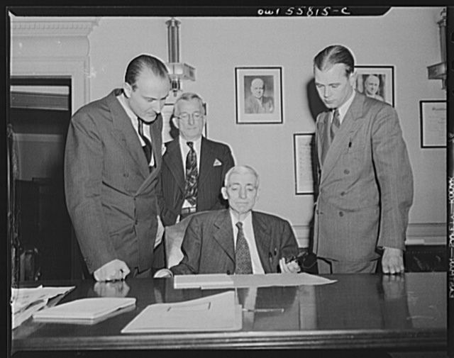 Washington, D.C. Mario Verdi (left), OWI (Office of War Information) radio commentator for Italy, visiting Assistant Postmaster General Perdum. Left to right: Mario Verdi, S.M. Weben, Assistant Postmaster General Perdum and E.J. Mahoney of the OWI