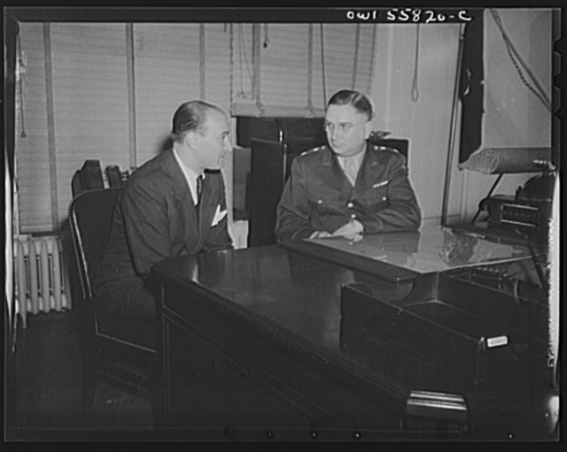 Washington, D.C. Mario Verdi (left), OWI (Office of War Information) radio commentator for Italy, visiting Provost Marshal General Brine