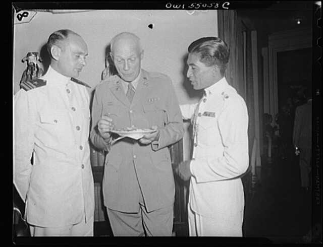 Washington, D.C. Present at an informal reception at the Thai Legation in celebration of the nineteenth birthday of King Ananda of Thailand, who is currently residing in Switzerland, were, left to right, Lieutenant Commander Edmond L. Taylor, United States Navy, who has recently returned from Far Eastern duty, Lieutenant Colonel G.V. Kendall, United States Army, on leave from the European theatre, and Lieutenant Colonel Mom Luang Kharb Junjara, Military attache to the Thai Legation