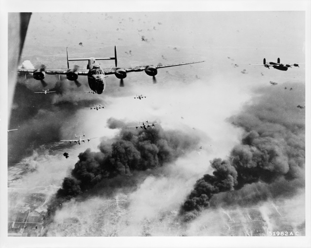 [Waves of Consolidated B-24 liberators of the 15th AAF fly over the target area, the Concordia Vega Oil refinery, Ploești, Romania, unmindful of bursting flak, after dropping their bomb loads on the oil cracking plant, on 31 May '44]