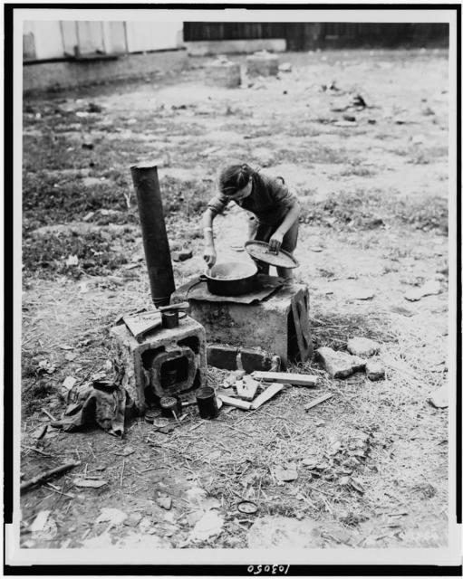 A Ukrainian girl prepares a meal for her family on a make shift stove in a concentration camp at Salzburg, Austria / Signal Corps photo.
