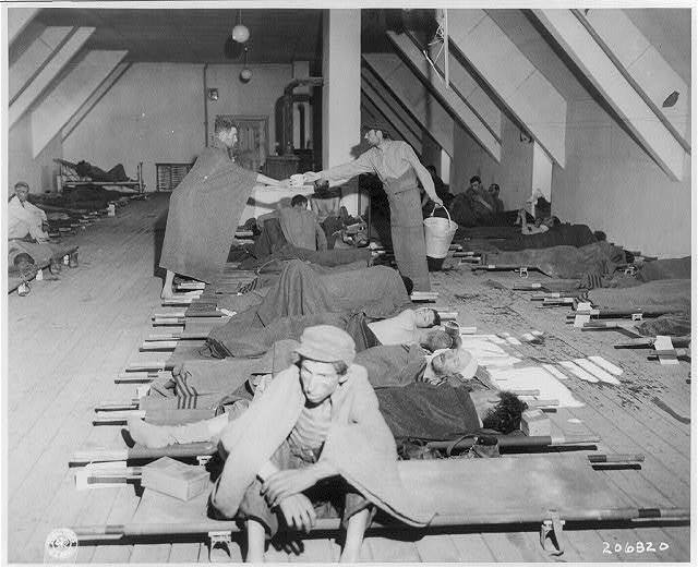 [Austria, May 1945 - Hungarian Jews after removal from Nazi concentration camps to facilities provided by US Army 121st Evacuation Hosp.: men lying on cots inside building (#206820)]
