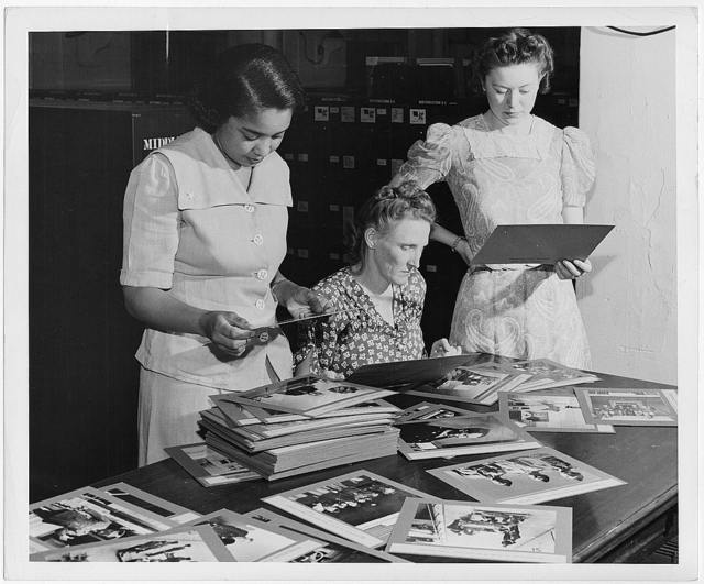 Fredrycka Weaver, Rachel Paczkowzki, and Katryna Lee Kritzer examining photographs at the Washington office of the Overseas Branch of the U.S. Office of War information
