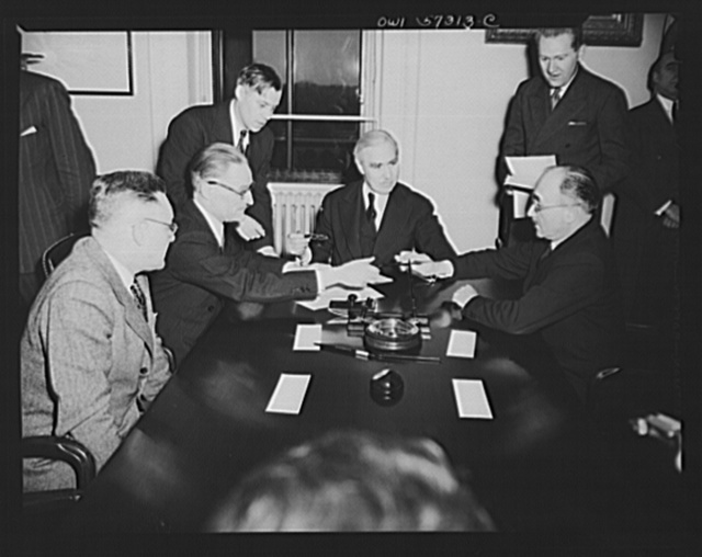 French conclude agreement on lend-lease and reverse lend-lease. Jean Monnet, representative of the French Provisional Government signs agreements. Left to right: Judson Hannegan, F.E.A., Henri Bonnet, French Ambassador, Joseph C. Grew, Undersecretary of State and Jean Monnet