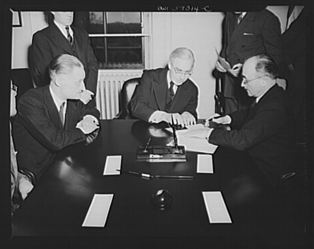 French conclude agreement on lend-lease and reverse lend-lease. Jean Monnet, representative of the French Provisional Government signs agreements. Left to right: Henri Bonnet, French Ambassador, Joseph C. Grew, Undersecretary of State and Jean Monnet