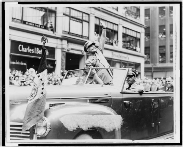 [General Dwight D. Eisenhower waves from automobile in parade to people in buildings above] / World Telegram photo by Fred Palumbo.