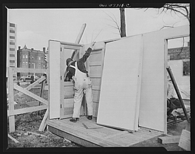 Houses for Britain. Assembling pre-fabricated temporary emergency house of the type which it is planned to ship to Great Britian under lend-lease to alleviate an acute housing shortage in Britian due to bombings. This model house was erected at Scott Circle, Washington, D.C. by the Federal Public Housing Authority of the National Housing Agency which will undertake procurement of the dwelling under a directive from FEA to whom materials for 30,000 units have been allotted by War Production Board