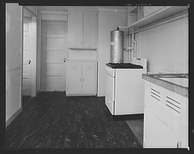 Houses for Britain. Kitchen in  prefabricated model house erected at Scott Circle, Washington, D.C. by the Federal Public Housing Authority of the type of temporary, emergency dwellings which it is planned to ship to Great Britain under lend-lease.  Door at left opens into a larder, with louvers for ventilation from the outside which will serve in place of a refrigerator or ice box. Built-in cupboards length of right wall. Between stove and sink is space for laundry cabinet to be installed in England. Door straight ahead leads into living room. Linoleum in kitchen and bathroom to be omitted in England