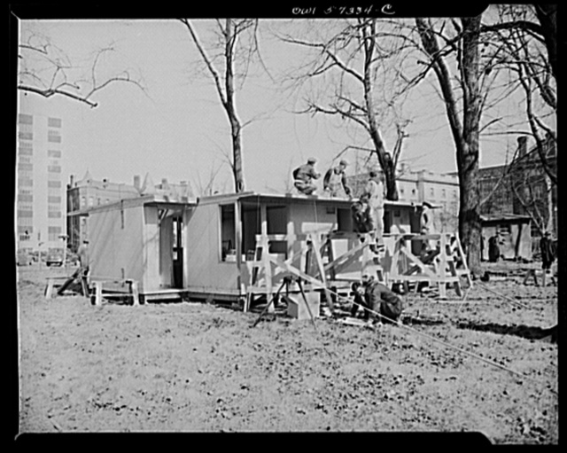 Houses for Britain.  Partially assembled pre-fabricated temporary emergency house of the type which United States will ship to Great Britain under lend-lease. War Production Board has allotted materials to the FEA for the production of 30,000 of these family dwellings. Designed for a minimum use of critical materials, including lumber. Procurement of the buildings will be undertaken by the Federal Public Housing Authority