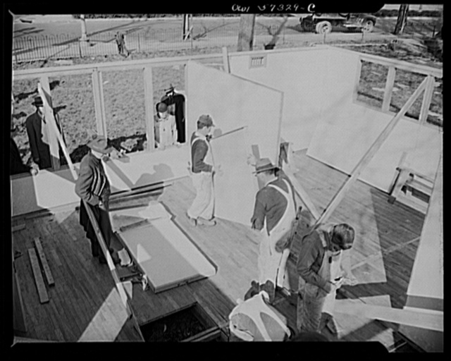 Houses for Britain. Partition panels going into place in model house erected by the Federal Public Housing Authority at Scott Circle, Washington, D.C. It is planned to ship 30,000 of this type of prefabricated, temporary emergency dwelling to Great Britain under lend-lease to alleviate acute housing shortage there due to bombings. Materials have been allotted by  War Production Board and the Federal Public Housing Authority of the National Housing Agency will undertake the procurement of the houses, acting under a directive from FEA