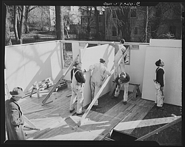 Houses for Britain. Putting a partition in place in the pre-fabricated house erected at Scott Circle, Washington, D.C. of the type of temporary emergency family dwelling 30,000 of which are to be shipped by the United States to Great Britain under lend-lease. Containing two bedrooms, bathroom, living room, and kitchen, the houses were designed to reduce to a minimum the use of critical materials, including lumber
