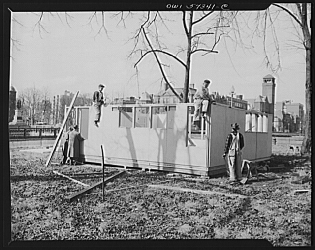 Houses for Britain. With outside walls in place, workmen prepare to put on roof panels on model house erected by the Federal Public Housing Authority at Scott Circle, Washington, D.C. It is planned to ship 30,000 of these pre-fabricated temporary emergency family dwellings to Great Britain under lend-lease. Materials have been allotted by the War Production Board and procurement of the buildings will be undertaken by the Federal Public Housing Authority