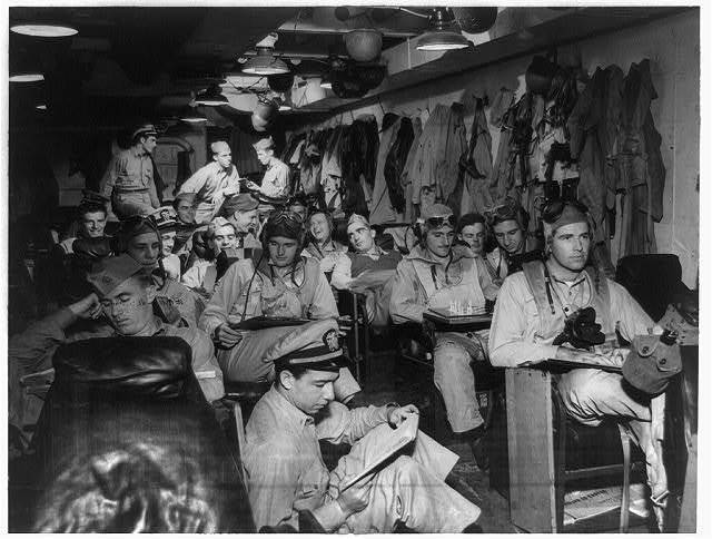 [Navy fighter pilots in the ready room of their aircraft carrier before a strike somewhere in the Pacific in a recent battle operation]