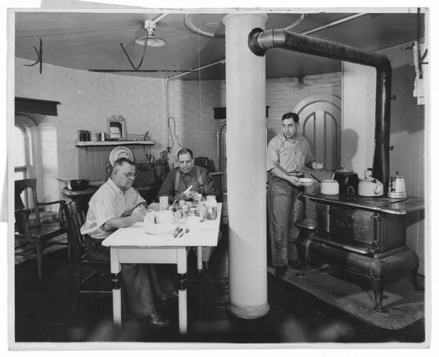 Ralph Rexinger, and Joaquim H. Brits starting to eat while Olaf Andersen cooking at stove / World Telegram photo by Dick De Marsico.