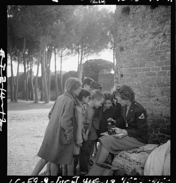 [Toni Frissell, sitting, holding camera on her lap, with several children standing around her, somewhere in Europe]