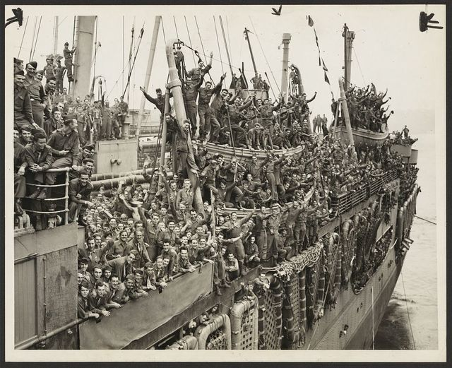 Troops of the 20th Armored Division and units of the 9th Army whoop it up between raindrops as the SS John Ericsson nears Pier 84, North River / World Telegram & Sun photo by Al Ravenna.