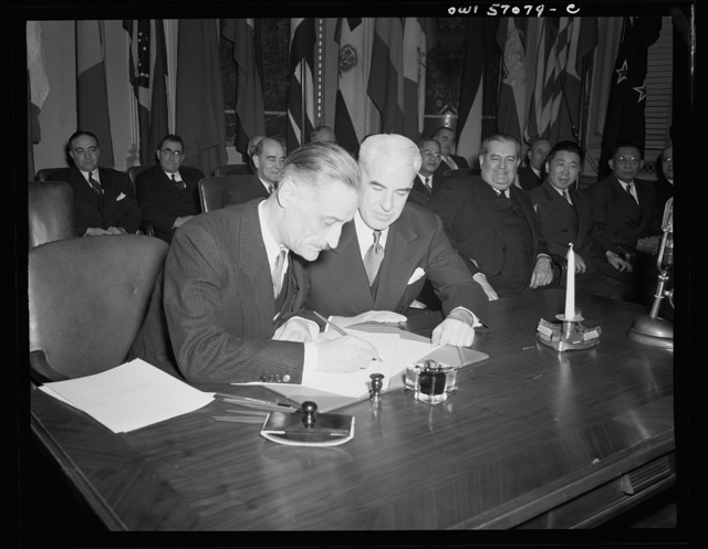 Washington, D.C. Henri Bonnet, French Ambassador, signing the United Nations declaration for France at the State Department