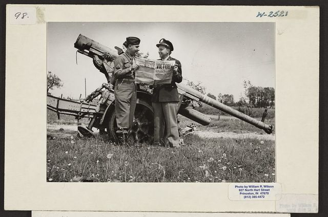 [William R. Wilson (right) and brother Cpl. Jack Wilson (left) standing by a German 88 mm gun at Verdun, France on VE Day]