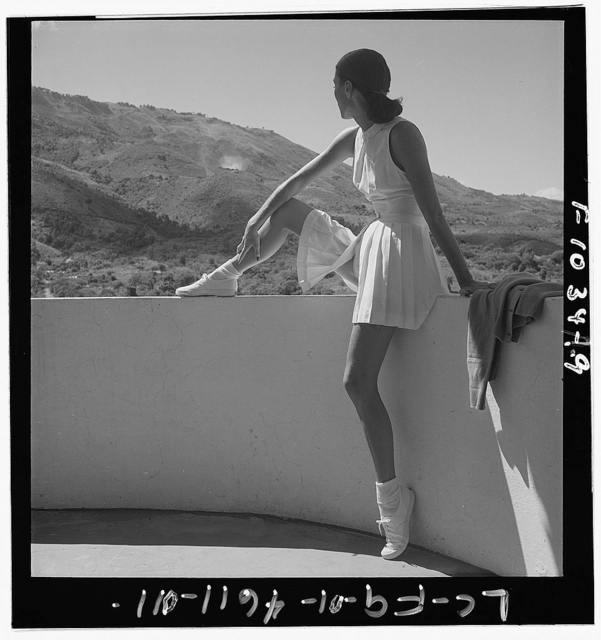 [Woman wearing tennis outfit, seated on wall, with one leg on top of wall, looking at the mountains behind her]